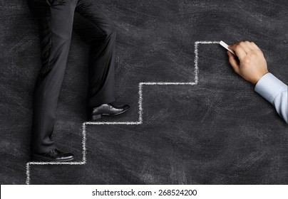 Business man climbing up on hand drawn staircase