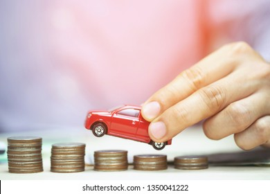 Business man and close up hand holding model of toy car red on over a lot money of stacked coins - insurance, loan and buying car finance concept. buy and installments down payment  a car