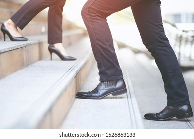 business man close-up legs walking up and working woman go down the stair in city. walk by in opposite directions in rush hour to work in office a hurry. During the first morning of work. stairway