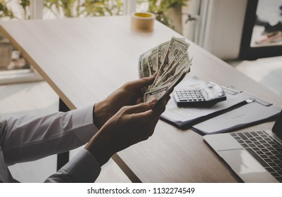 Business man counting dollar bill money in office