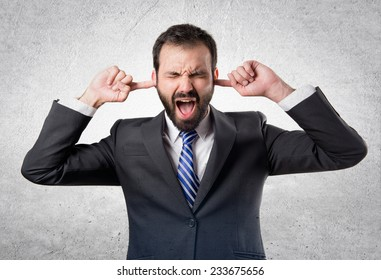 business man covering her ears over textured background
