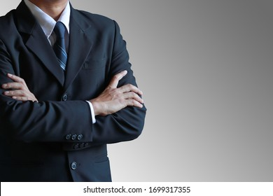 Geschäftsmann mit Querarm auf grauem Hintergrund.