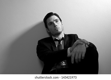 Business man in deep thought resting against the wall