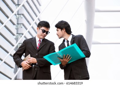 Business man are discussing together in city. They are looking at files.