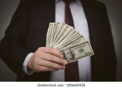 Business Man Displaying a Spread of Cash over a white vintage background