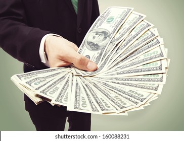 Business Man Displaying a Spread of Cash over Vintage Green Background