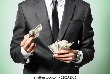Business man displaying a spread of cash over a green background