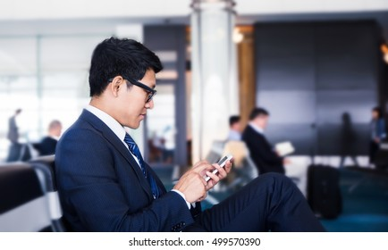 business man is Doing Business on mobile phone, while is sitting in Airport near window with sun rays during his business trip.