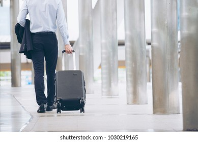 Business man Dragging suitcase luggage bag,walking to passenger boarding in Airport.Working young man travel to work.Asian tourist men wearing black suit pull trolley bag. Businessman Travel concept.