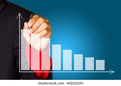 Business man drawing red decline graph over blue background - business and finance concept