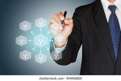 Business man drawing social network structure on blue background