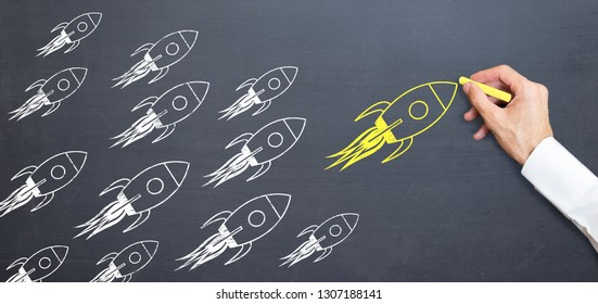 business man is drawing yellow rocket on blackboard with chalk. rising concept