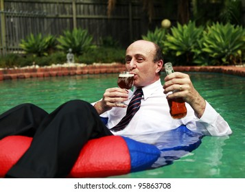 A business man dressed in business attire in a swimming pool, floating with a beer in one hand and a glass filled with beer in the other in the sun.