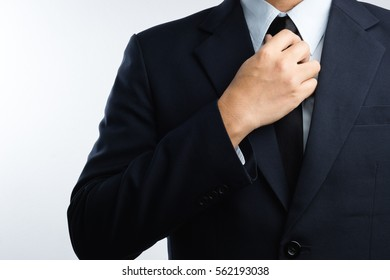 Business man dressing up and adjusting tie on white background