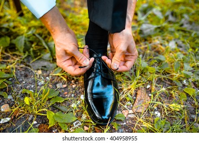 Business man dressing up with classic, elegant shoes. Groom wearing shoes on wedding day, tying the laces and preparing on the grass.