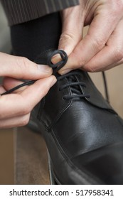 Business man dressing up with classic, elegant black shoes and tying his laces