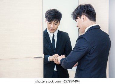 Business man dressing up for work in front of the mirror