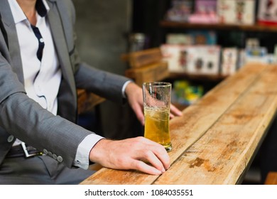 A business man drinking beer alone while sitting at bar counter in pub.