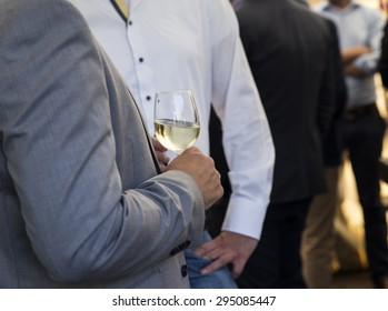 Business man drinking glass of white wine at party