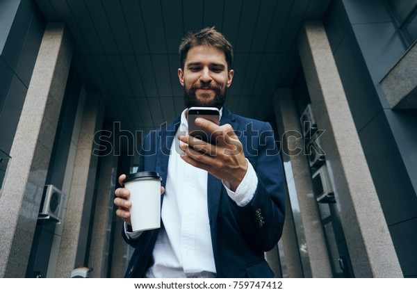 business man drinks coffee and checks news on phone.