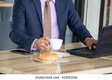 Business man eat coffee at work laptop,