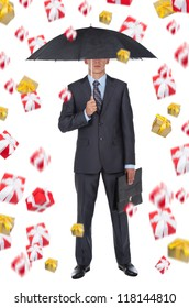 Business man in elegant modern suit hold an umbrella rain of gift box present fly fall down around, isolated over white background, concept of holiday
