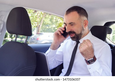 Business man / employee  talking on mobile phone while sitting in the back seat of car. He is happy.