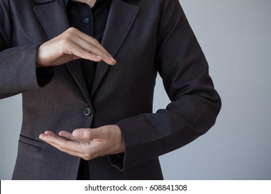 Business man with empty hand presenting something on grey background