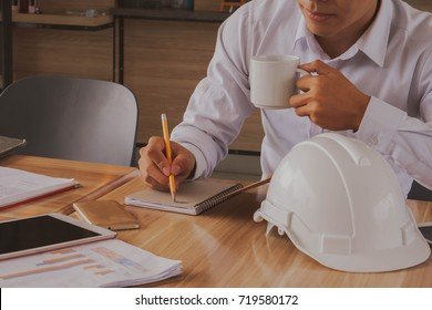 Business man or engineer  or architect hands with contract and pen, coffee and white  safety helmet.