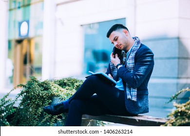 Business man is enjoying the beautiful weather while sitting on the city bench with his coffee and tablet, calling for a car taxi ride, e-hailing