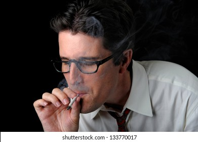A business man enjoys a long pull on a joint.