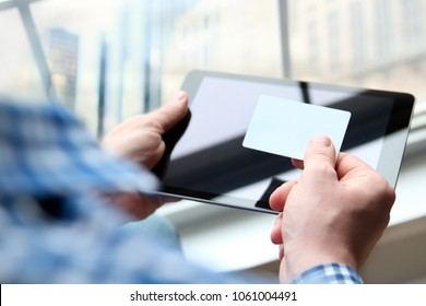 business man entering data of a credit card . On-line shopping on the internet using a digital tablet