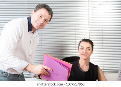 Business man explaining something to a woman in an office