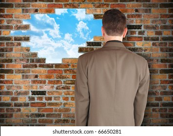 A business man is facing a brick wall with a hole of clouds in it representing escape. Use it for a freedom or barrier concept.