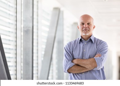 Business man facing the camera with arms crossed.