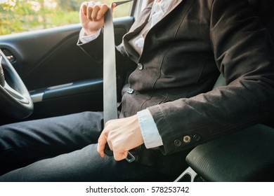 Business man fastening seat belt in the car