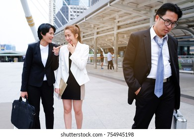 Business man feeling sad and serious. He unemployed. But Business woman laughing him.