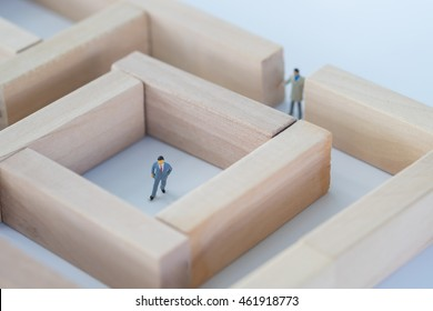 Business man figure stuck in the middle of the maze or labyrinth