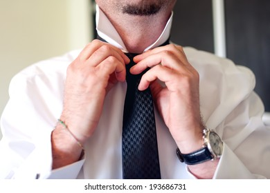 Business man fixing black tie on white shirt. Groom on wedding day fixing tie, vintage effect