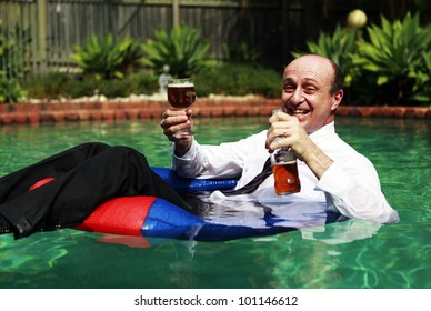 A Business man floating in a swimming pool, having just cracked the first beer of the day, still dressed in his business attire.