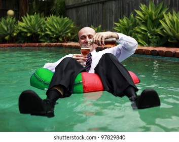 A Business man floating in a swimming pool, having just cracked the first beer of the day, still dressed in his business attire, pouring the beer into his mouth.