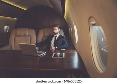 Business man flying on a private jet. Working onboard of the airplane. Successfull businessmen lifestyle. Concept about traders, affiliate marketing and sales people