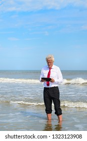 Business man in formal suit standing in sea working with tablet at the beach
