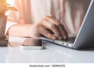 Business man or freelancer working on laptop computer and    mobile smartphone on white desk at home office, close up, online working concept