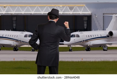 Business man in front of tow private jets