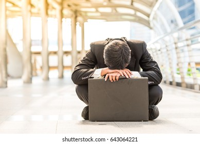 business man frustrated  he sad for lost work and sit on street upset fail unhappy after Fired from job in black suit