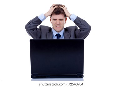 business man is frustrated on a table with a laptop, pulling his hair