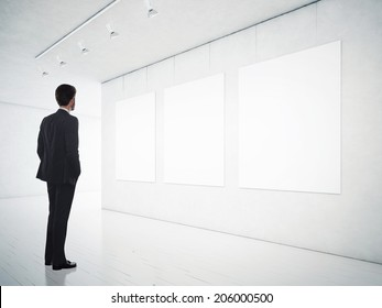 Business man in gallery room looking at empty frames