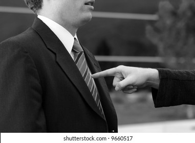 Business man is getting pointed in the chest by another businessman in front of a blue office building