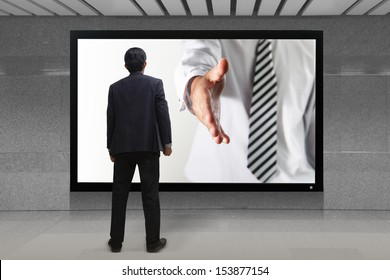 Business man gives a handshake out of TV screen